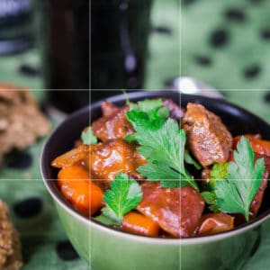 In this image of Guinness stew, I have created a bit of height and color with the green garnish; the photo fills a little more than half the photo, and the food is positioned in the lower right third of the photo.